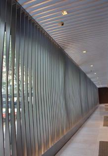 A custom metal screen wall interior sunshade system supplied by DAMS Inc. (formerly Doralco Architectural Metals) was installed across the glass curtainwall behind the check-in area on the second floor of the Hyatt Regency Chicago.
